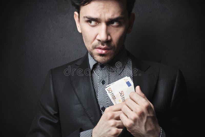 Hombre que roba un poco de dinero fotografía de archivo libre de regalías