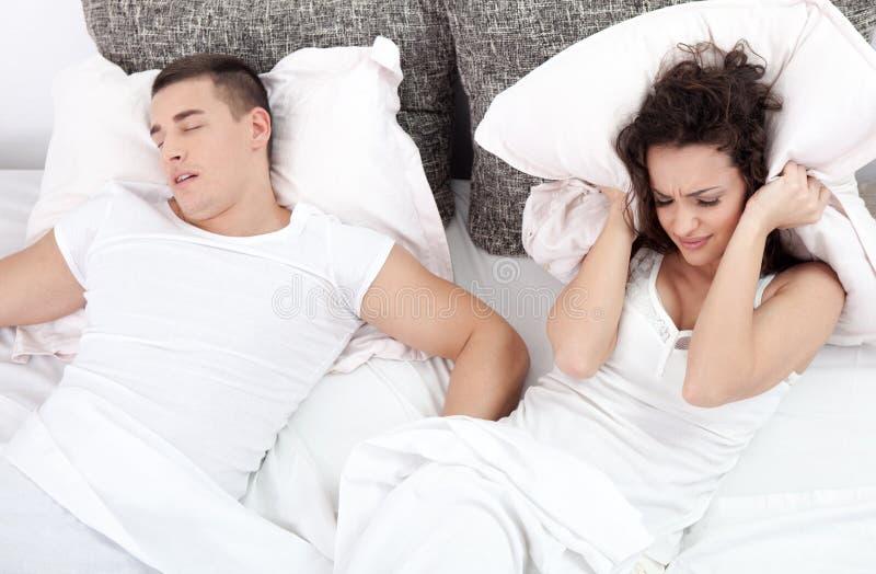 Hombre que ronca y mujer joven. Pares que duermen en cama. foto de archivo