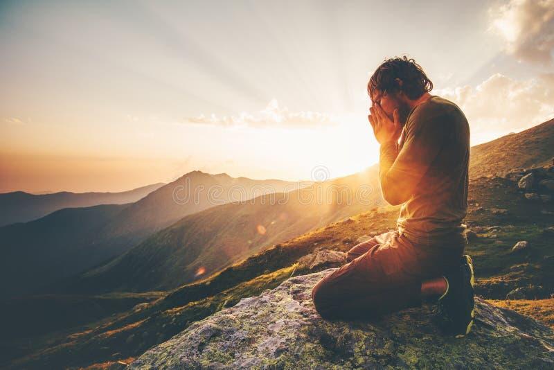 Hombre que ruega en las montañas de la puesta del sol imagen de archivo libre de regalías