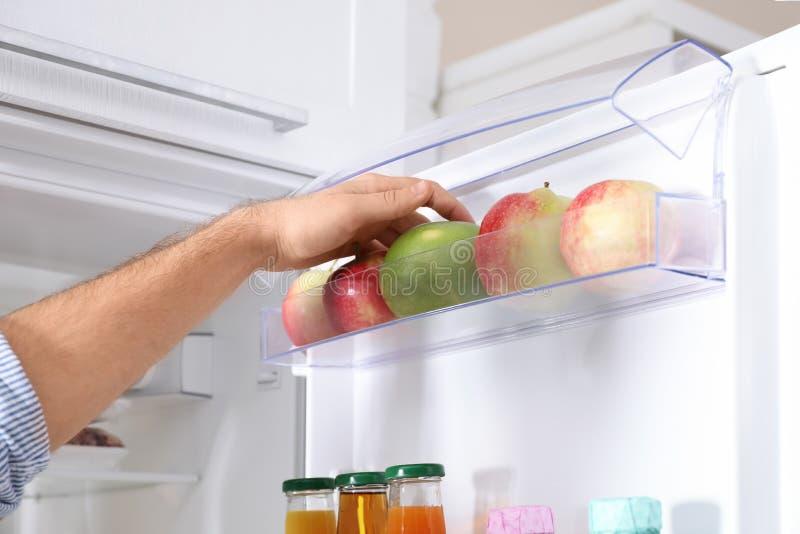Hombre que saca la fruta del refrigerador en cocina, imágenes de archivo libres de regalías