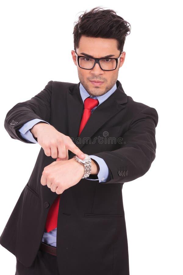 Hombre que señala a su reloj fotografía de archivo