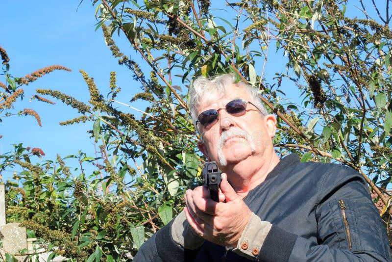 Hombre que señala un arma hacia la cámara. imagenes de archivo