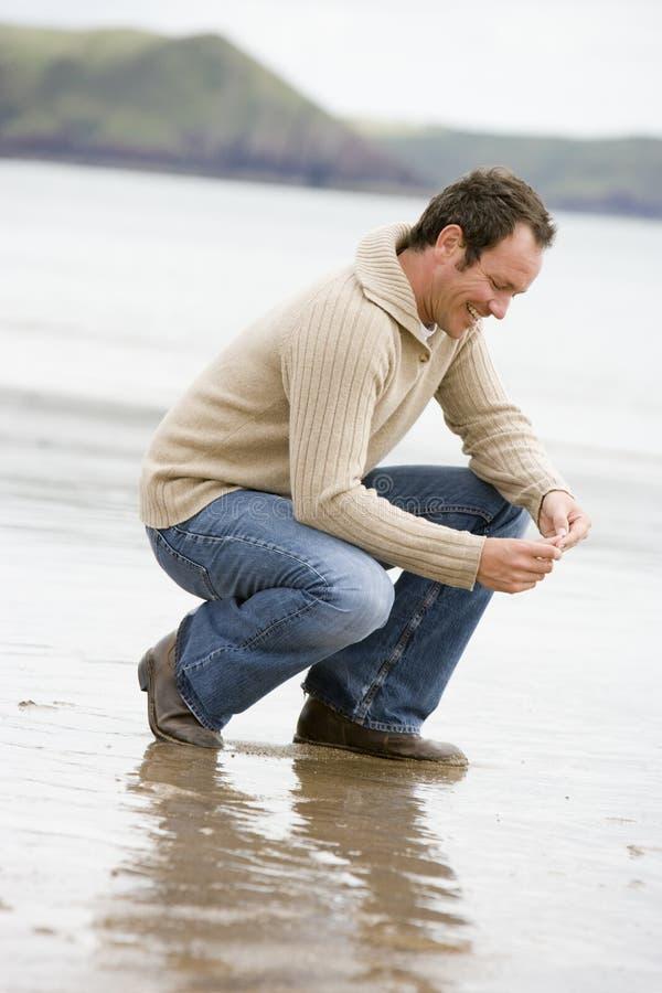 Hombre que se agacha en la playa imagenes de archivo