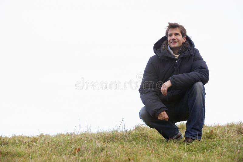 Hombre que se agacha en parque imagen de archivo libre de regalías