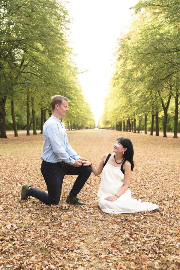 Hombre que se arrodilla delante de su novia y que hace propuesta de matrimonio en parque imagen de archivo libre de regalías