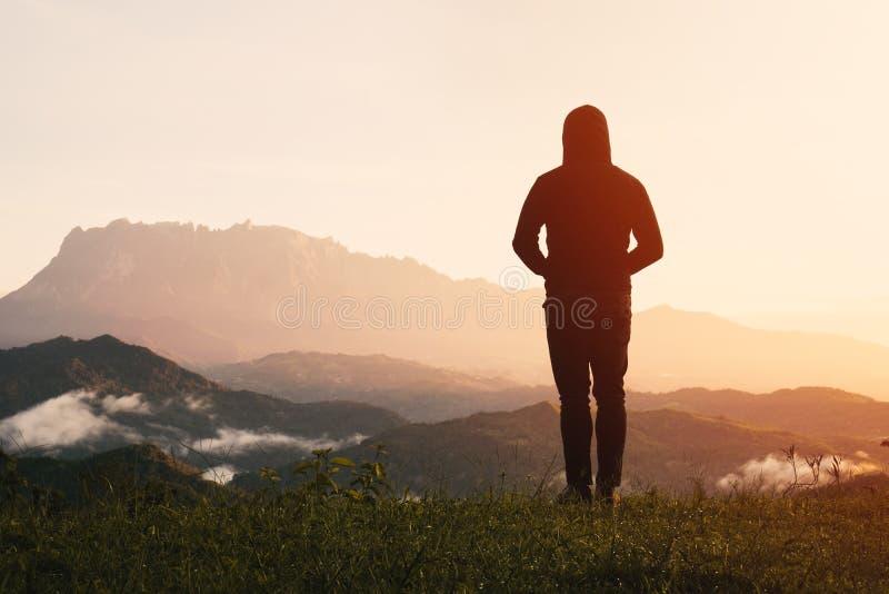 Hombre que se coloca de mirada del Monte Kinabalu en salida del sol fotografía de archivo