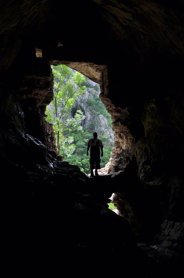Hombre que se coloca delante de una entrada de la cueva fotografía de archivo