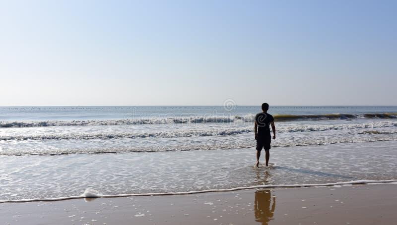 Hombre que se coloca en el mar con las ondas imagenes de archivo