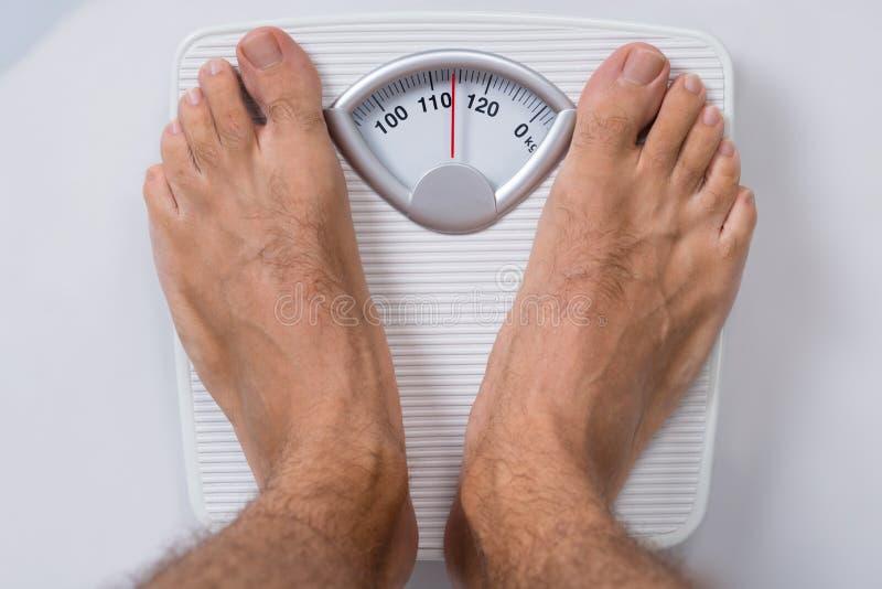 Hombre que se coloca en escala del peso foto de archivo