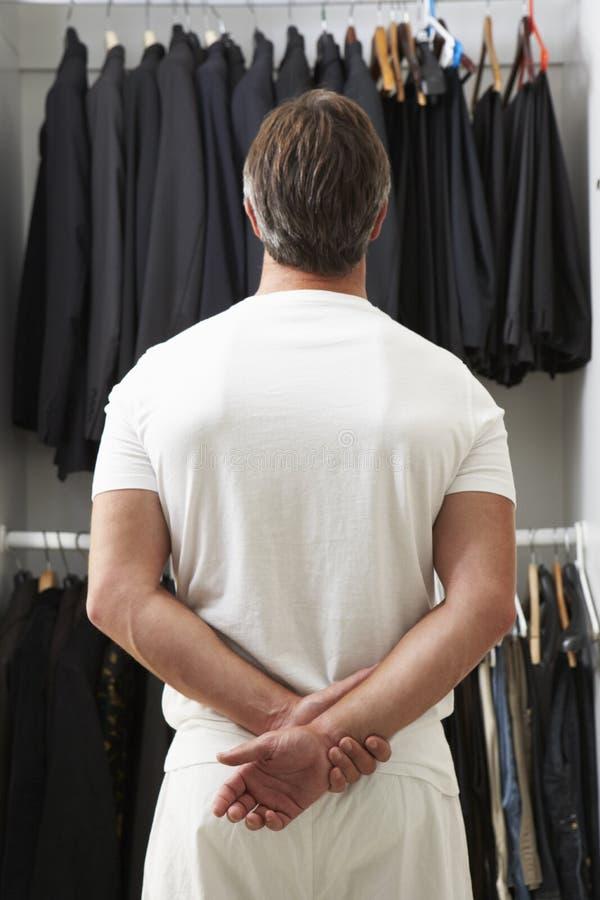 Hombre que se coloca en Front Of Wardrobe Choosing Clothes imagen de archivo