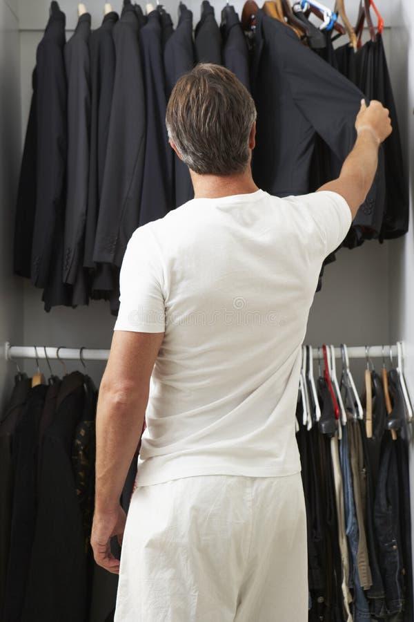 Hombre que se coloca en Front Of Wardrobe Choosing Clothes imagen de archivo libre de regalías