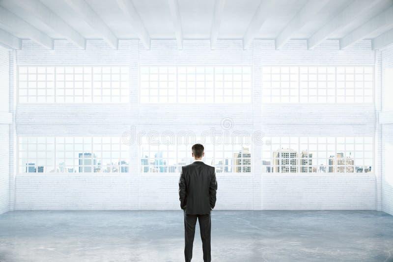 Hombre que se coloca en hangar vacío stock de ilustración