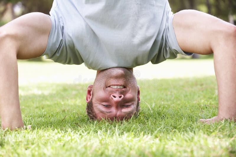 Hombre que se coloca en la cabeza en jardín fotos de archivo