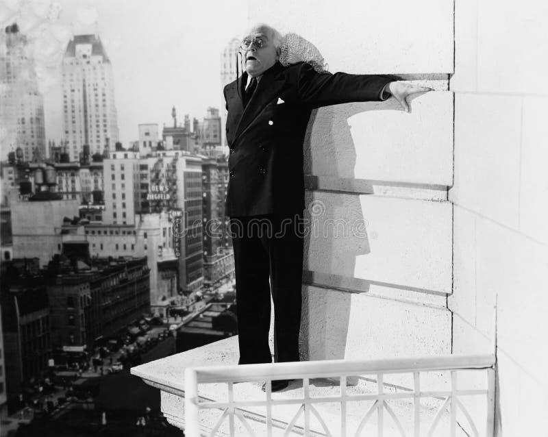 Hombre que se coloca en la repisa de un edificio y que parece temido (todas las personas representadas no son vivas más largo y n imagenes de archivo