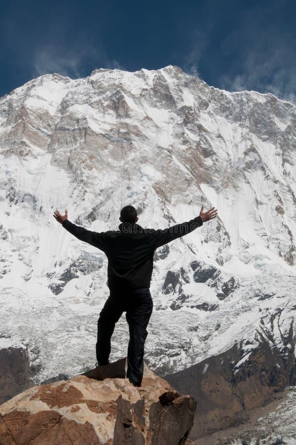 Hombre que se coloca en roca delante de la montaña imagenes de archivo