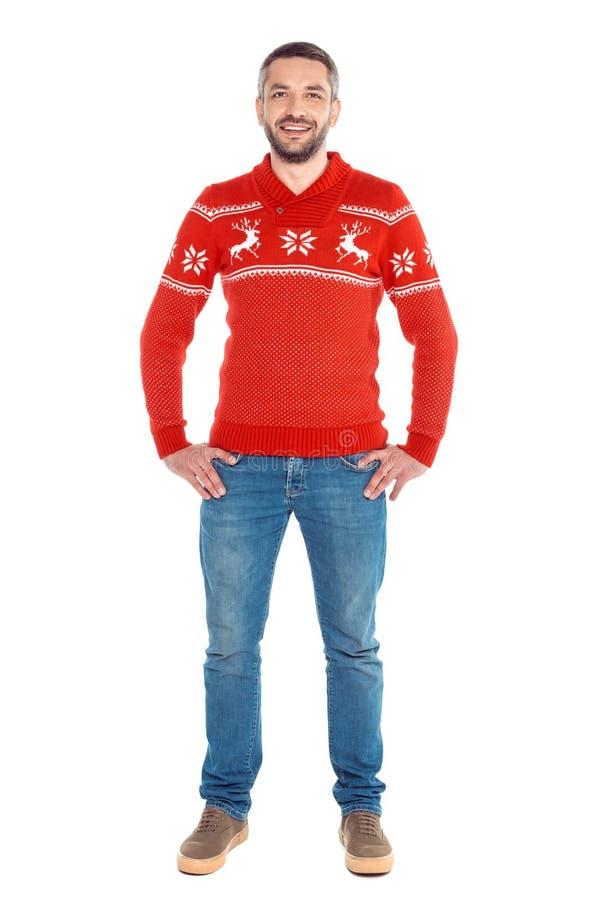 hombre que se coloca en suéter rojo de la Navidad, fotos de archivo libres de regalías