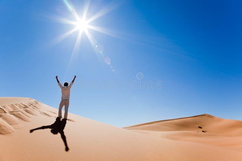 Hombre que se coloca en una duna de arena foto de archivo libre de regalías