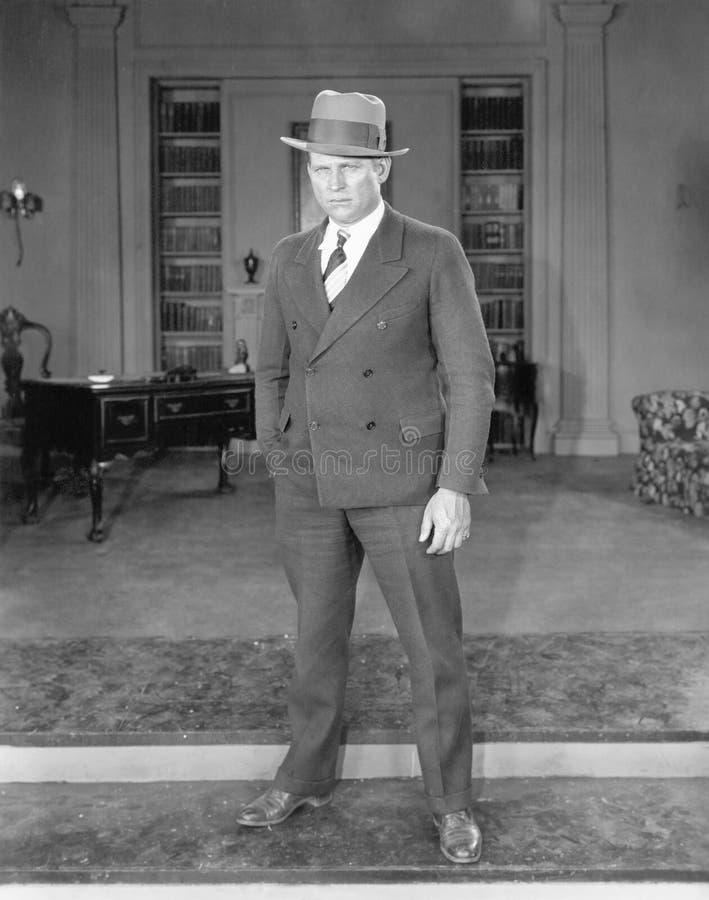 Hombre que se coloca en una oficina (todas las personas representadas no son vivas más largo y ningún estado existe Garantías del foto de archivo