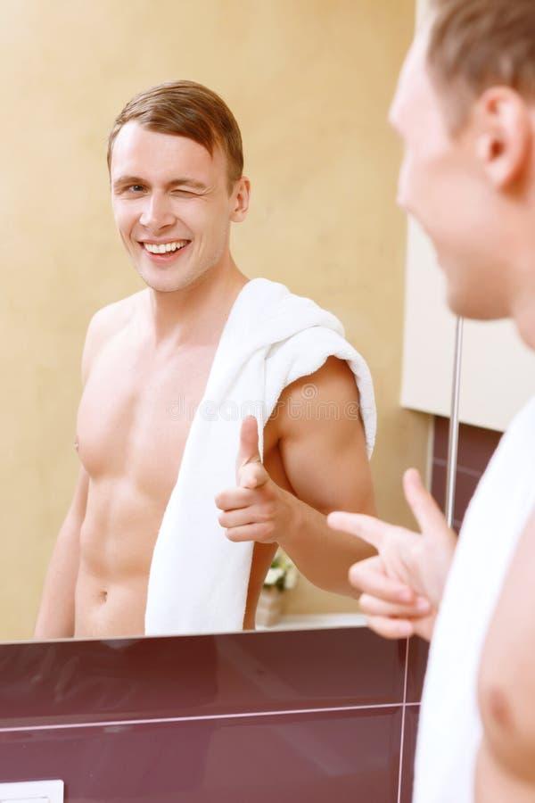 Hombre que se da el frente del guiño I del espejo imagen de archivo