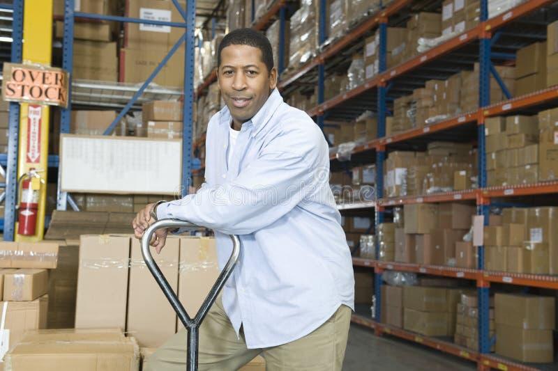 Hombre que se inclina en la carretilla en Warehouse foto de archivo libre de regalías