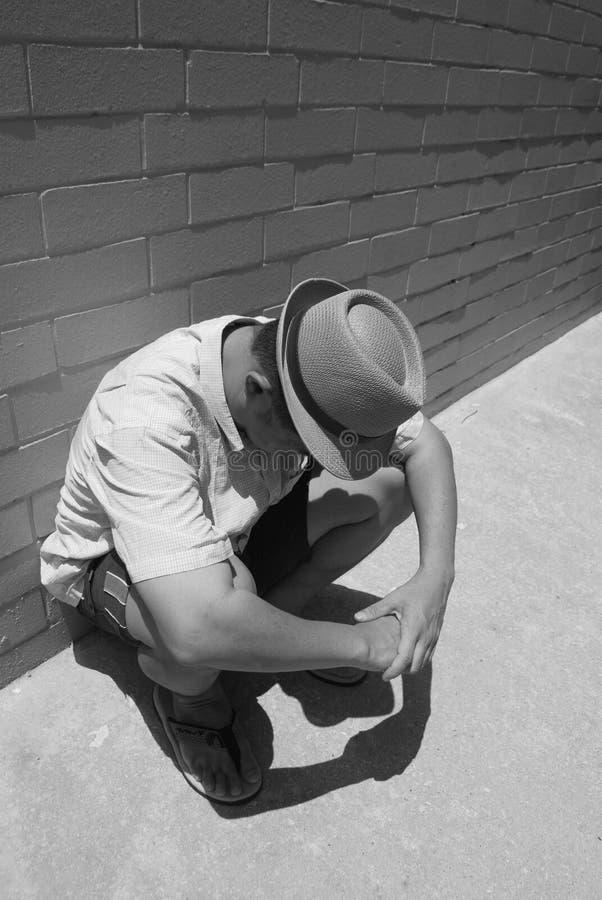 Hombre que se pone en cuclillas imagenes de archivo