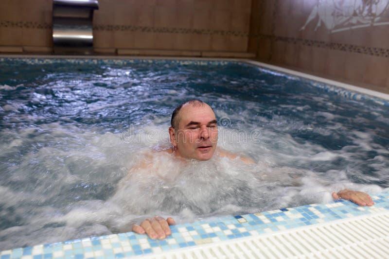 Hombre que se reclina en Jacuzzi fotografía de archivo