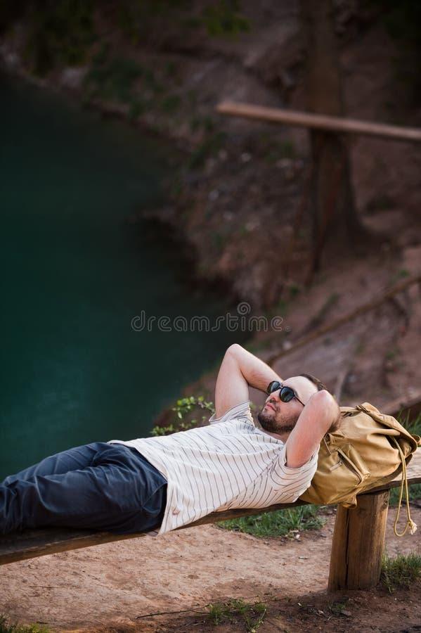 Hombre que se relaja afuera Llevando una camiseta blanca, los pantalones oscuros, gafas de sol, un individuo joven se están acost imagen de archivo libre de regalías