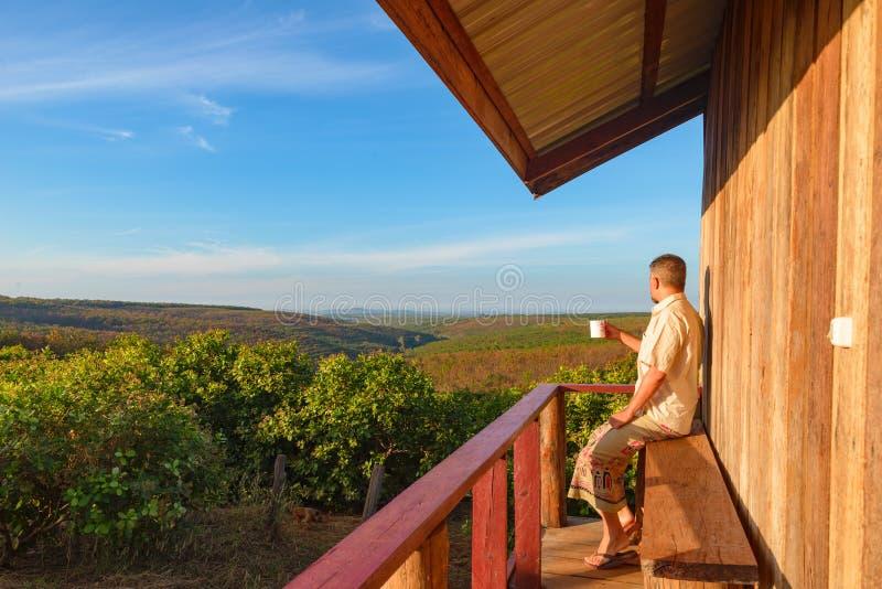 Hombre que se relaja en el campo, sentándose en cabina de madera del balcón, café de consumición, paisaje de observación en la sa imágenes de archivo libres de regalías