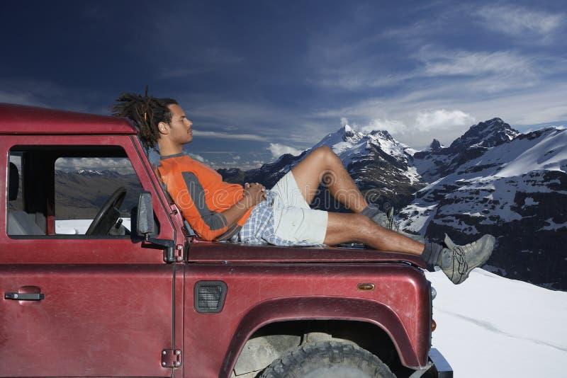 Hombre que se relaja en el coche Hood Against Mountains fotos de archivo libres de regalías