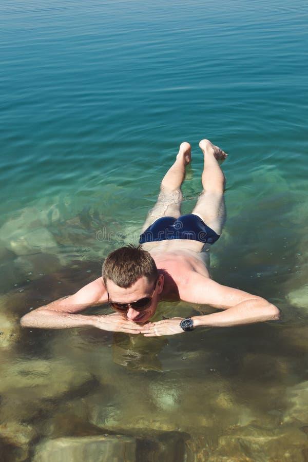 Hombre que se relaja en el mar muerto de la superficie del agua Reconstrucción del turismo, concepto sano de la forma de vida Med fotos de archivo