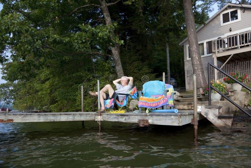 Hombre que se relaja en la casa del lago fotografía de archivo