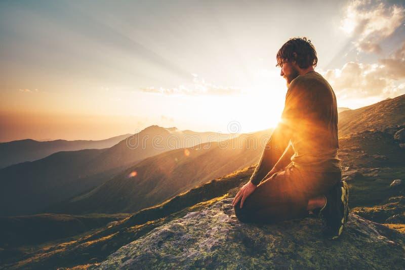 Hombre que se relaja en la forma de vida del viaje de las montañas de la puesta del sol imágenes de archivo libres de regalías
