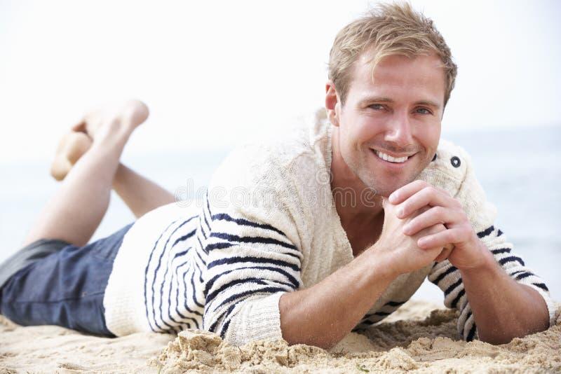 Hombre que se relaja en la playa fotografía de archivo