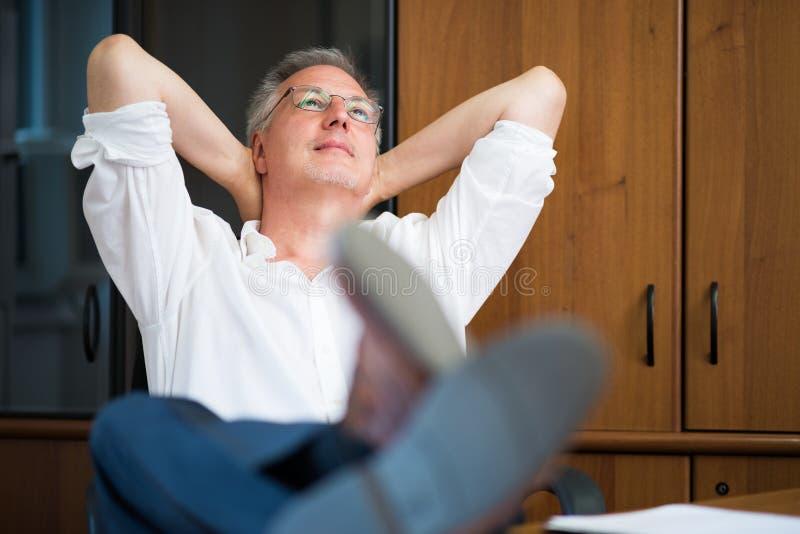 Hombre que se relaja en su oficina después de trabajo imágenes de archivo libres de regalías