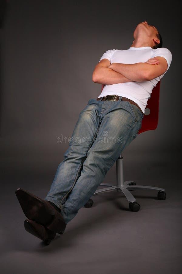 Hombre que se relaja en taburete imagen de archivo