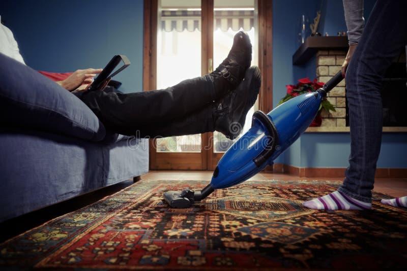 Hombre que se relaja mientras que mujer que hace tareas en el país imagen de archivo libre de regalías