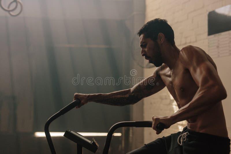 Hombre que se resuelve en la bicicleta estática en el gimnasio foto de archivo