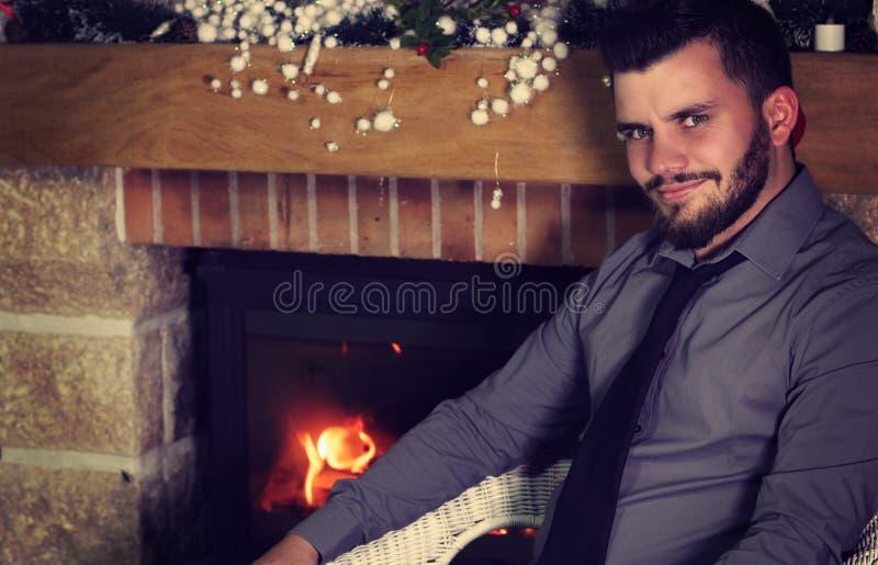 Hombre que se sienta al lado de la chimenea foto de archivo libre de regalías