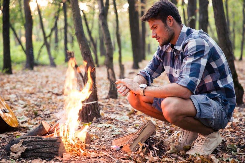Hombre que se sienta cerca de hoguera en el bosque foto de archivo