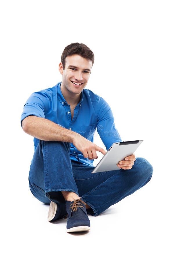 Hombre que se sienta con la tableta digital imagenes de archivo