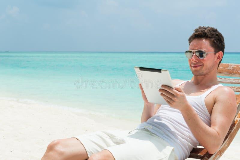 Hombre que se sienta con la tableta en la playa imagenes de archivo