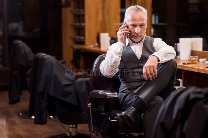 Hombre que se sienta del negocio mayor que habla en el teléfono móvil foto de archivo libre de regalías