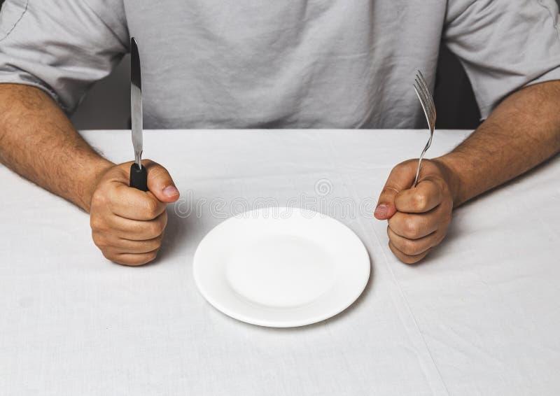hombre que se sienta detrás de una tabla con la bifurcación y del cuchillo en las manos y la placa vacía, hora de comer - concept fotografía de archivo libre de regalías