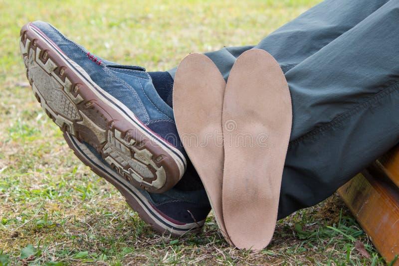 Hombre que se sienta en banco de parque con las plantillas ortop?dicas situadas cerca de las piernas Sano rel?jese en la naturale fotos de archivo