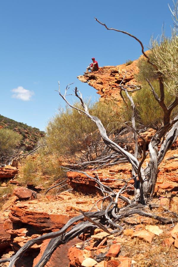 Hombre que se sienta en el borde de la roca foto de archivo libre de regalías