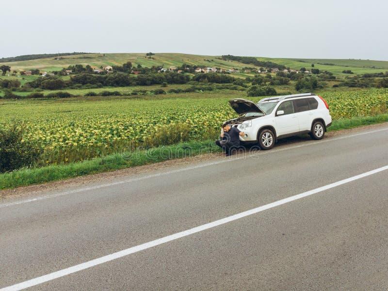 Hombre que se sienta en el camino cerca del coche quebrado coche de la parada que intenta para la ayuda imagen de archivo
