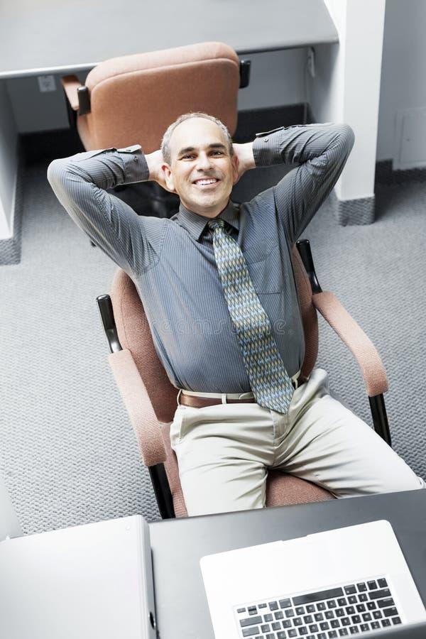 Hombre que se sienta en el escritorio de oficina imagenes de archivo