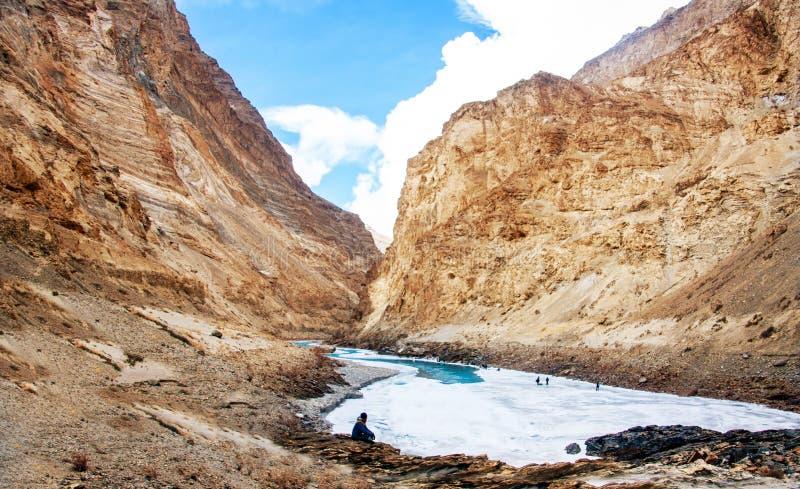 Hombre que se sienta en el lado del río Río congelado de Zanskar y montaña hermosa Curva de flujo del río fotografía de archivo