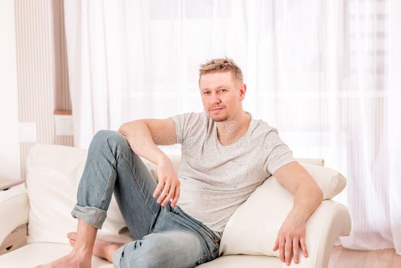Hombre que se sienta en el sofá en dormitorio foto de archivo