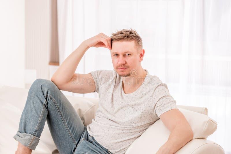 Hombre que se sienta en el sof? en dormitorio imagenes de archivo